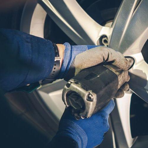 A Technician Removes A Tire.
